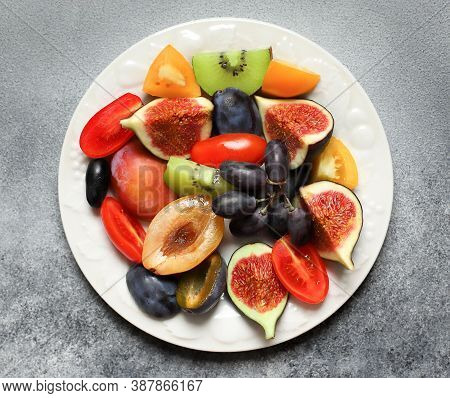Sliced Plums, Figs, Yellow And Red Tomatoes, Kiwis, Grapes On A White Porcelain Plate, Top View. Sum