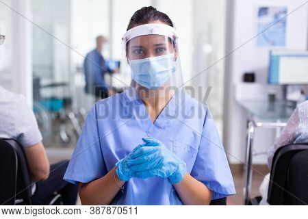 Medical Physician Wearing Face Mask Against Coronavirus Looking At Camera In Hospital Waiting Area.