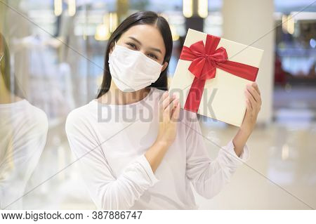Woman Wearing Protective Mask Holding A Gift Box In Shopping Mall, Shopping Under Covid-19 Pandemic,