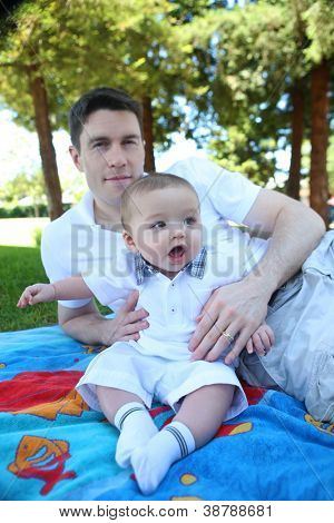 A father sitting with his cute baby boy in the park