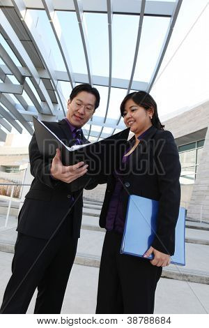 An ethnic man and woman business team looking at notebook