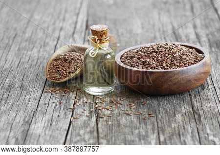 Heap Of Flax Seeds Or Linseeds In Spoon Or Bowl With Glass Of Flax Seed Oil On Rustic Backdrop. Flax