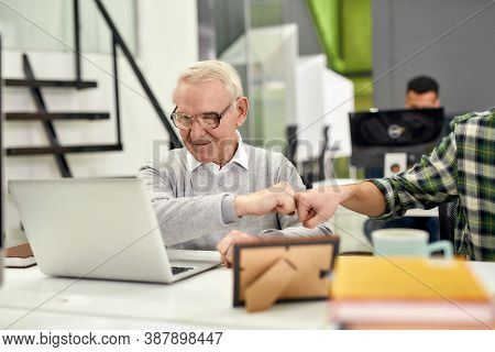 Aged Man, Senior Intern Looking At The Screen Of His Laptop And Doing A Fist Bump With Colleague, Fr