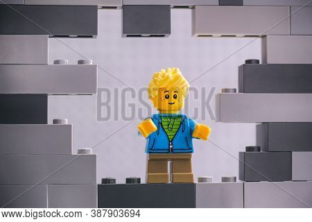Tambov, Russian Federation - August 26, 2020 Lego Boy Minifigure Looking Through A Hole In Gray Wall