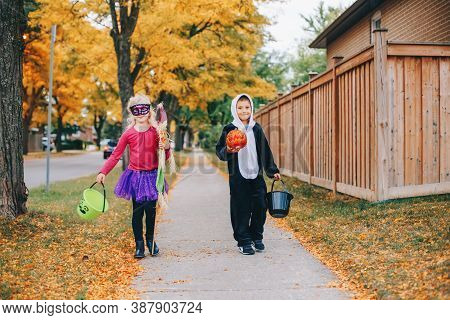 Trick Or Treat. Happy Children Going To Trick Or Treat On Halloween Holiday. Kids Boy And Girl In Pa