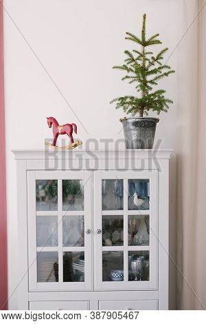 Christmas Tree In A Metal Bucket, Vintage Wooden Red Toy Horse On A White Dresser In The Interior Of