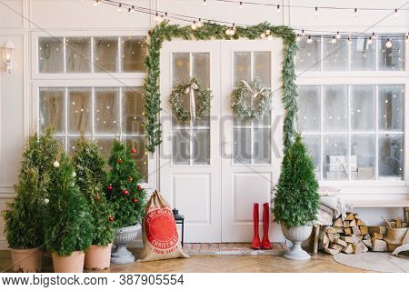 Porch With A White Door In Christmas Decorations And Christmas Trees. Spruce Garlands Around The Doo