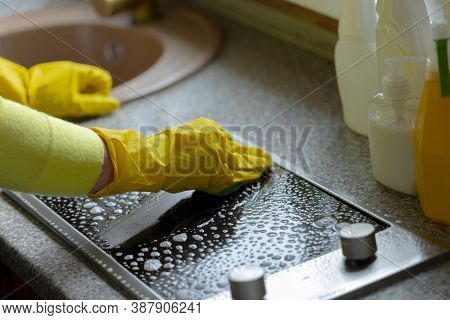 Close Up Female Person In Yellow Wear Cleaning House Wipes Kitchen Worktop, Washes Induction Stove W
