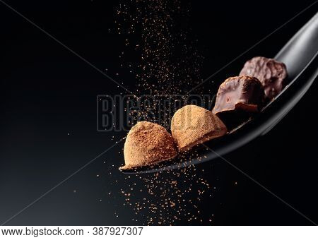 Chocolate Candy Sprinkled With Cocoa Powder On A Dark Background. Copy Space.