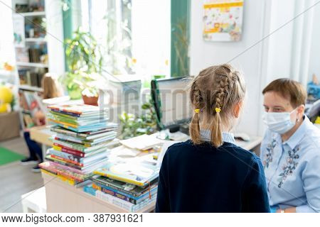 Russia Moscow 25.09.20 Little Girl Talks To Librarian In Face Mask, Asks,loos For Book With Fairy Ta