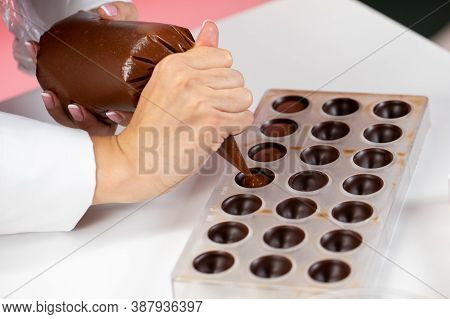 Top View Of Chocolatier Pouring Caramel Filling Into Chocolate Mold Preparing Luxurious Handmade Bel