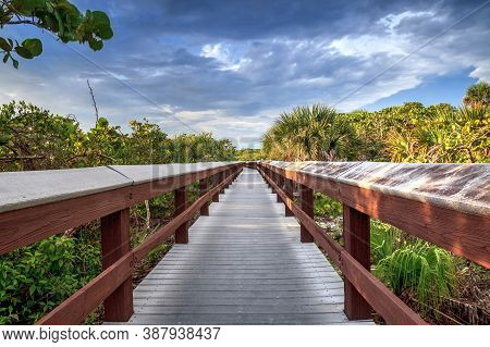 Boardwalk Leads Down To The White Sand Of Barefoot Beach In Bonita Springs, Florida