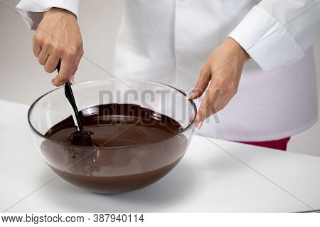 Close Up Mixing And Stirring Dark Melted Chocolate Isolated On White Background. Chocolatier Make Or