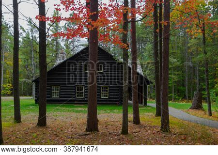 Log Cabin In The Woods. Traditional Log Cabin In A Remote Forest Framed By Autumn Foliage. This Is A