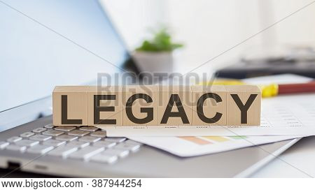 Legacy Wooden Cubes With Letters On A Laptop Keyboardwith Charts , Magnifier