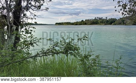Trees And Green Grass Grow On The Banks Of The River. The Water Flows Calmly. There Are Picturesque