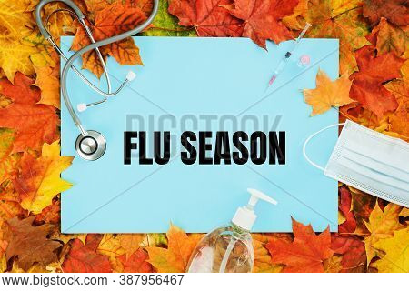 Flu Season Text On Blue With Fall Leaves. Flu Season Or Second Wave. Face Protective Mask, Sanitizer