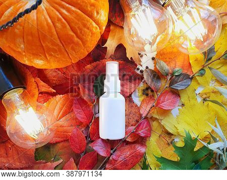 Mockup Of White Plastic Spray Bottle Pumpkin, Magic Lights And Bright Autumn Leaves. Atmospheric Fal