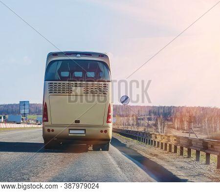 Bus Goes On Highway In Beams Of Sun
