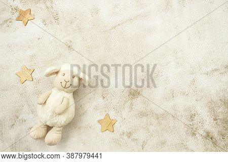 Toy Lamb And Wooden Stars On Pastel Background. Motherhood Concept. Top View, Flat Lay Composition.
