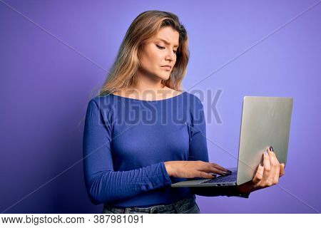 Young beautiful blonde woman working using laptop over isolated purple background with a confident expression on smart face thinking serious