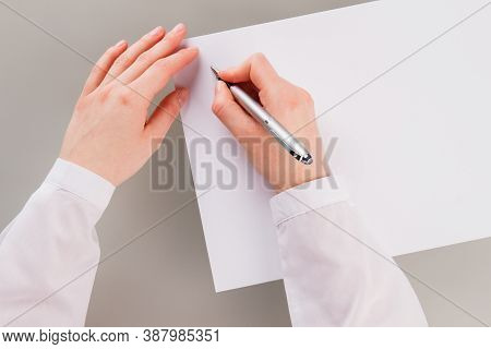 Female Hand Holding Pen And Writing On Blank Paper. Business Womans Hand Writing On Paper Sheet.
