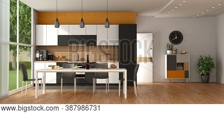 Modern Black And White Kitchen Against Orange Wall, With Dining Table,open Door And Sideboard On Bac