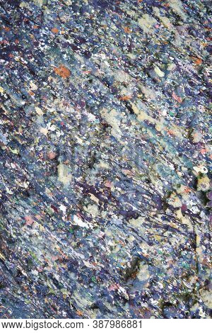 Grunge texture of stone surface stained with motley paint spots.