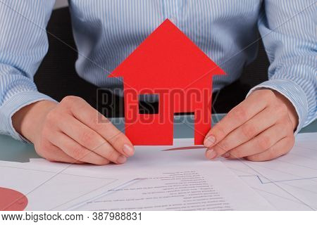Business Woman Holding Red Paper House. Real Estate Agent Holding Model House Over Table With Docume