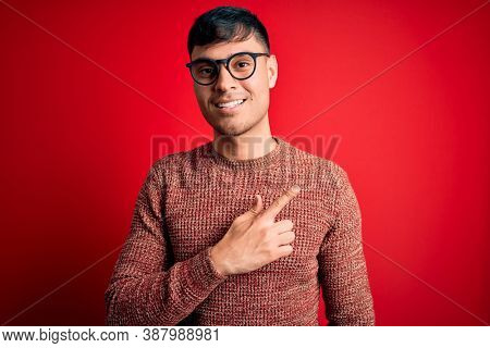 Young handsome hispanic man wearing nerd glasses over red background cheerful with a smile on face pointing with hand and finger up to the side with happy and natural expression