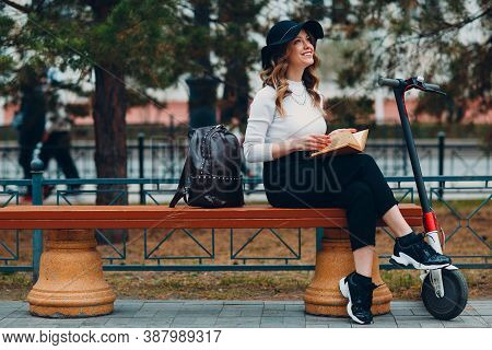 Young Woman Reading Book And Sitting On Bench With Electric Scooter At The City