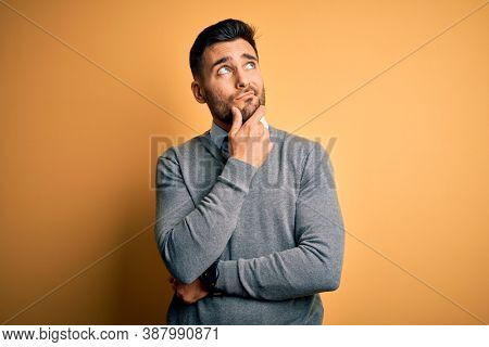 Young handsome businessman wearing elegant sweater and tie over yellow background with hand on chin thinking about question, pensive expression. Smiling with thoughtful face. Doubt concept.