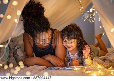African mother and cute smiling girl using digital tablet while lying in illuminated tent in kid bedroom. Cheerful ethnic woman and lovely daughter on video call under a cozy hut. Lovely little girl.