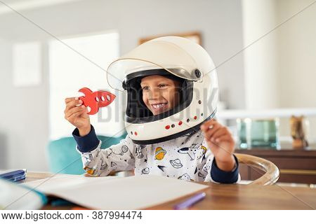 Little boy wearing an astronaut helmet costume and playing with a spaceship while doing homework. Cute kid in astronaut pajamas with toy rocket playing and dreaming of becoming a spacemen.