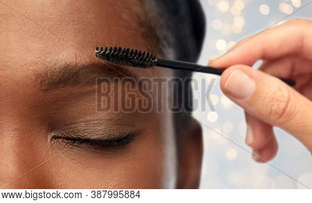 beauty, make up and cosmetics concept - close up of face of young african american woman and hand with mascara brush applying eyebrow shadows over festive lights background