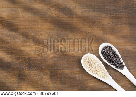 White Sesame And Black Sesame Seed - Sesamum Indicum. Wooden Background