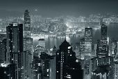 Hong Kong city skyline at night with Victoria Harbor and skyscrapers illuminated by lights over water viewed from mountain top in black and white. poster