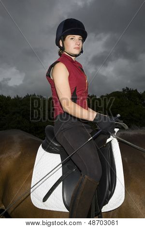 Side view portrait of a female horseback rider sitting on brown horse