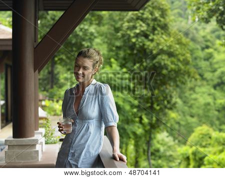 Smiling young woman with a glass of water in veranda against blurred trees