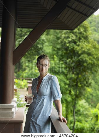 Young woman with a glass of water in veranda against blurred trees