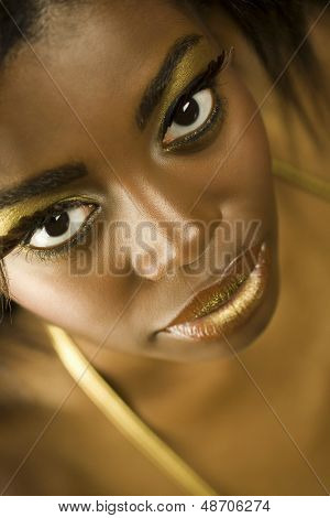Closeup portrait of an African American woman with golden makeup