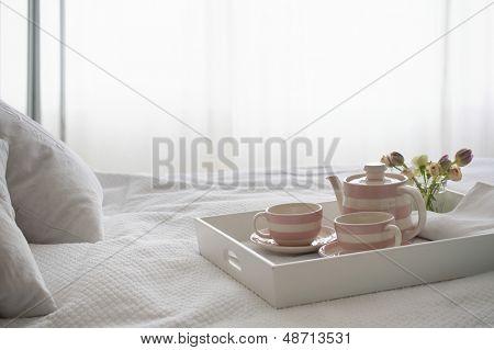 Pink striped teaset on breakfast tray in bedroom