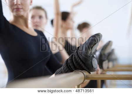 Row of ballet dancers practicing at the barre in rehearsal room