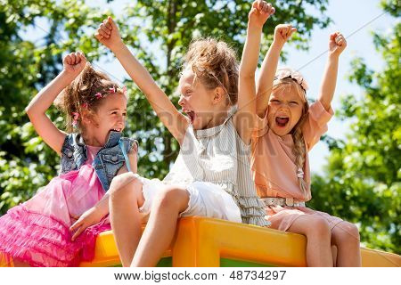 Young Girls Shouting And Raising Arms Outdoors.