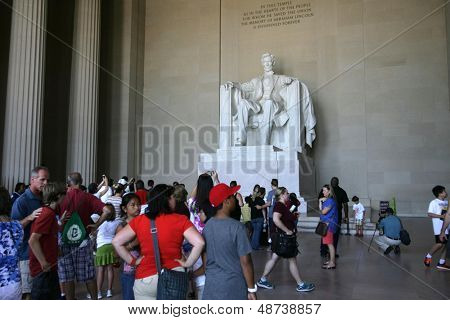 WASHINGTON, D.C. - JULY 29: Tourists walk near the statue of Abraham Lincoln at the Lincoln Memorial on July 29, 2013 in Washington, D.C. The memorial was dedicated in 1922.