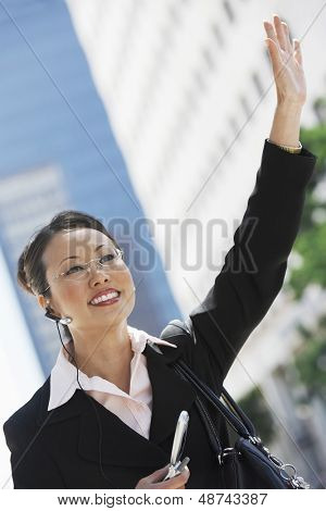 Asian businesswoman hailing cab while using cellphone with hands free device