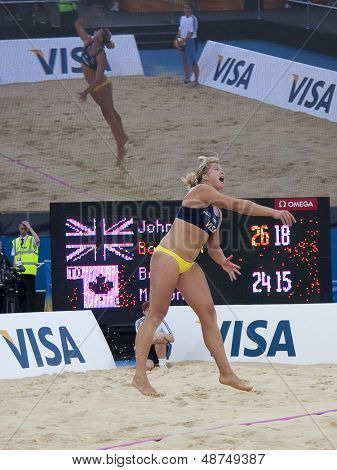 12/08/2011 LONDON, ENGLAND, Lucy Boulton (GBR) serves with her image being projected on a large screen behind her during the FIVB Beach Volleyball, at Horse Guards Parade, Westminster, London.