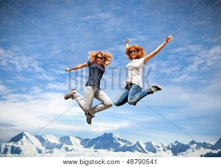 Two beautiful young woman jumping together in summer sunny day. Himalayas , Nepal.
