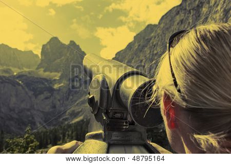 Woman looks through telescope  in the alps of Austria poster