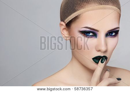 Portrait of young beautiful woman with stylish fancy green make-up and hairnet on her head